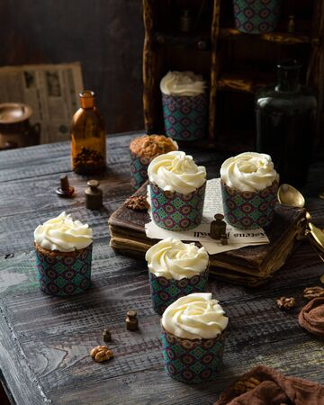 Delicious homemade carrot cupcakes in blue paper cups with white beautiful icing standing on rustic wooden table with vintage book, spoons, brown textile, brass weights, walnuts, cinnamon, glasses