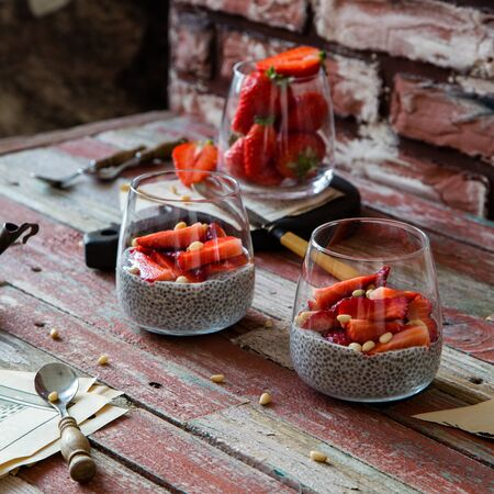 Two glasses with homemade super food chia pudding with cut strawberries on red rustic wooden table with glass of berries, knife, seeds opposite red brick wall. Breakfast still life