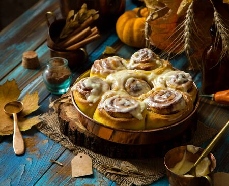 cinnamon rolled pumpkin buns with white sticky glaze on top in copper round pan on wooden stand on rustic blue wooden table with pumpkins, autumn leaves, cinnamon, selective focus, thanksgiving 写真素材