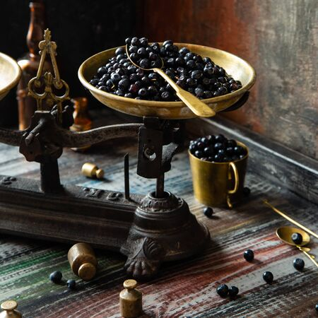 Ripe juicy dark blue berries on brass plate on vintage black scales with golden spoon on wooden rustic table with gold cup of berries, spoons, weights opposite concrete dark wall 写真素材