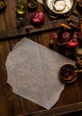 Overhead shot of process of cooking or baking some vegetarian meal with baking paper on wooden brown table, basket of red onion, bottle with oil, bowl of spices, preserves, plate with flour