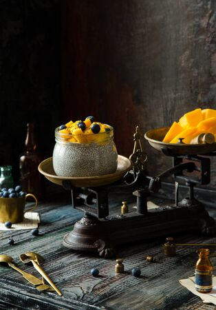 Homemade glass bowl with super food chia pudding with cut mango, blueberries on top stand on vintage scales on rustic wooden table with cup of berries, spoons, seeds opposite concrete dark wall 写真素材