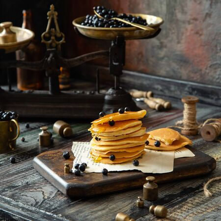 Homemade pancakes with honey and dark blue berries on wooden board on wooden rustic table with vintage black scales, gold cup of berries, spoons, weights opposite concrete dark wall