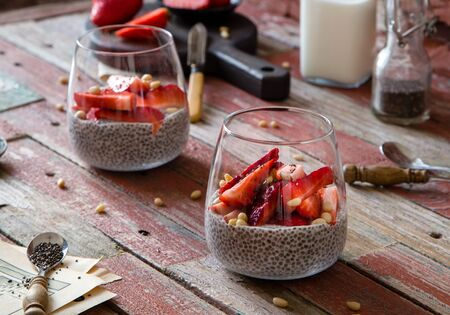 Two glasses with homemade super food chia pudding with cut strawberries on red rustic wooden table with berries, spoons, seeds, bottle with milk opposite red brick wall. Breakfast still life
