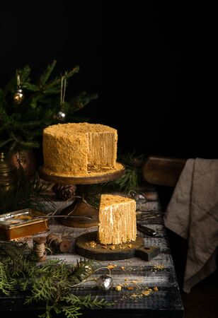 homemade tasty sliced traditional russian honey cake with vertical layers and white cream on wooden board on rustic grey table with fir tree branches, christmas toys
