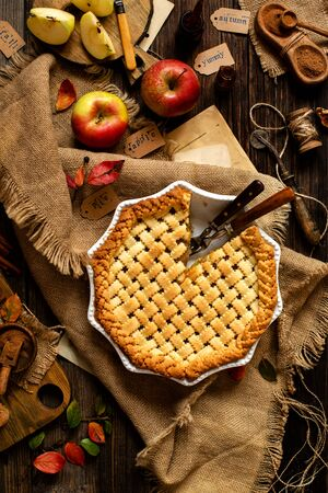 overhead shot of homemade thanksgiving warm baked sliced apple lattice pie crust on sackcloth on rustic wooden table with apples, spices, autumn leaves