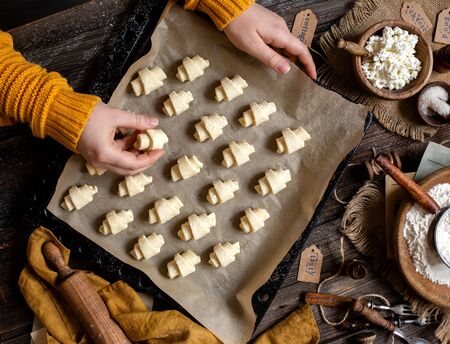 overhead shot of tasty unbaked rolled or bagels cookies on baking tray with parchment in woman hands on rustic wooden table with bowls of flour, sugar and cottage cheese, orange napkin Archivio Fotografico - 131730869