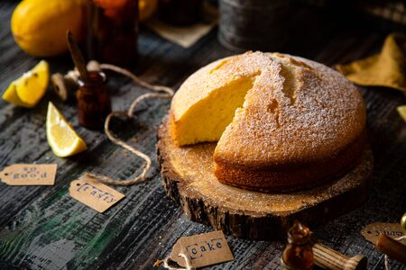 homemade tasty sliced baked lemon biscuit cake with powdered sugar on top stands on wooden board on rustic table with lemons, old bottles opposite concrete wall, selective focus