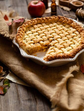 homemade thanksgiving warm baked sliced apple lattice pie crust on sackcloth on rustic wooden table with apples, spices, autumn leaves, selective focus Фото со стока