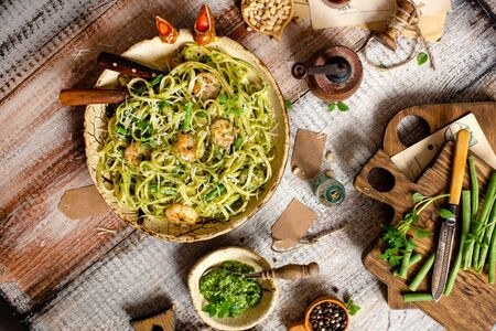 overhead shot of tasty homemade italian pasta with grilled shrimps, pesto sauce, parmesan cheese, fresh basil in ceramic bowl on wooden rustic table