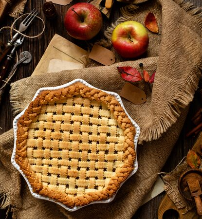 overhead shot of homemade thanksgiving warm baked apple lattice pie crust on sackcloth on rustic wooden table with apples, spices, autumn leaves 版權商用圖片