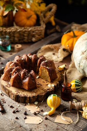 tasty homemade baked pumpkin bundt cake with chocolate on top stands on wooden board on rustic table with assorted colorful small pumpkins and autumn leaves in straw basket