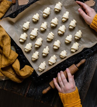 overhead shot of tasty unbaked rolled or bagels cookies on baking tray with parchment in woman hands on rustic wooden table with bowls of flour, sugar and cottage cheese, orange napkin Stok Fotoğraf
