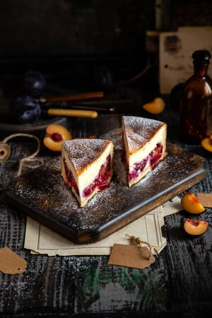 two slices of baked cheesecake or cottage cheese casserole on shortcrust with plums and powdered sugar stands on wooden board on rustic table with plums, old bottles opposite concrete wall Banco de Imagens