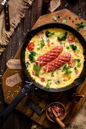 overhead shot of homemade tasty baked omelette or frittata with two sausages, broccoli, cherry tomatoes, basil, melted cheese in black skillet on wooden board on rustic table with sackcloth