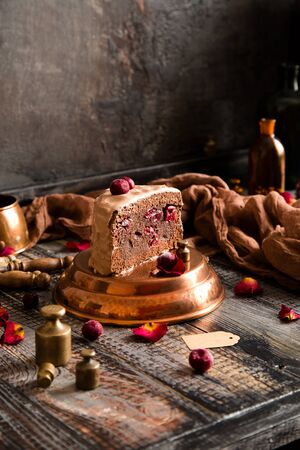 homemade chocolate sponge cake with chocolate creamy frosting and cherries inside and on top stands on copper pan on wooden table with brown napkin opposite concrete wall