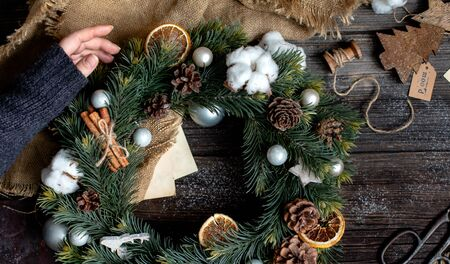 overhead shot of handmade christmas wreath with grey balls, pine cones, dried orange slices, cinnamon sticks on rustic wooden table with old scissors, sackcloth, new year toys