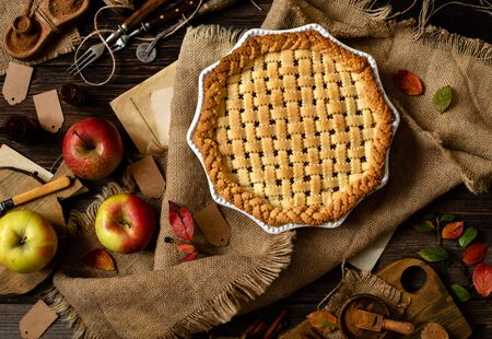 overhead shot of homemade thanksgiving warm baked apple lattice pie crust on sackcloth on rustic wooden table with apples, spices, autumn leaves Reklamní fotografie
