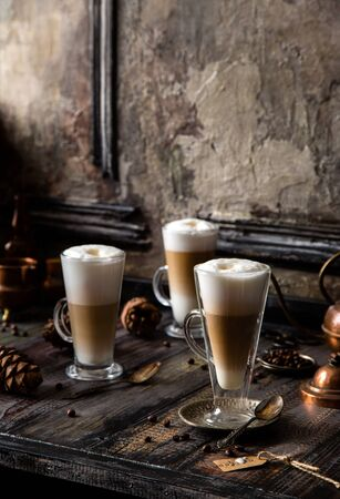 three tall glasses with foamy layered hot coffee drink latte on rustic wooden table opposite concrete wall
