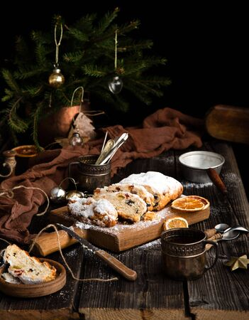 homemade traditional christmas dessert stollen with dried berries, nuts and powdered sugar on top stands on wooden board on rustic wooden table with fir tree branches, toys, vintage cups, spoons