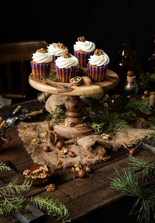 homemade carrot or pumpkin cupcakes with white cream and walnut on top in purple cupcake holders on wooden cake stand on rustic table with juniper branches, nuts, old bottles, spoons