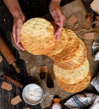 overhead shot of tasty crispy baked puff pastry round layers of homemade traditional Russian napoleon cake in woman hands on parchment on rustic wooden table Stok Fotoğraf