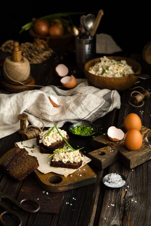 homemade tasty salad with hard boiled eggs, potato, green onion, mayonnaise in wooden bowl and on slices of bread on chopping board stands on rustic table with eggs, napkin, onion, selective focus Banque d'images - 132070101