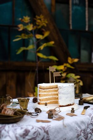 beautiful outdoor still life with naked biscuit multi layered sliced cake with white cream stands on table with beige tablecloth, brass vintage plates, cups in autumn garden