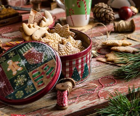 homemade delicious gingerbread cookies in vintage gift round metal box with christmas ornaments on wooden rustic red table with cup of coffee with foam, christmas tree branches opposite brick wall
