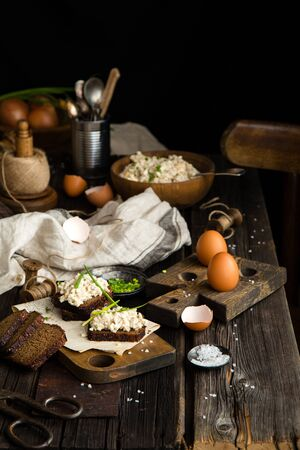 homemade tasty salad with hard boiled eggs, potato, green onion, mayonnaise in wooden bowl and on slices of bread on chopping board stands on rustic table with eggs, napkin, onion, selective focus Foto de archivo - 132619929