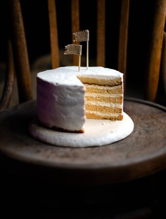 minimalistic dark food photography with tasty biscuit multi layered sliced cake with white cream stands on old chair