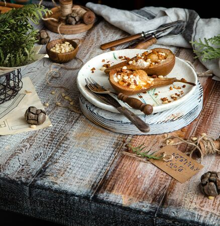 homemade baked pears cut in half with ricotta, granola, pine nuts on ceramic plate and wooden board stands on wooden table with grey napkin, forks, nuts