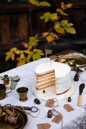 beautiful outdoor still life with biscuit multi layered sliced cake with white cream stands on table with beige tablecloth, brass vintage plates, cups in autumn garden