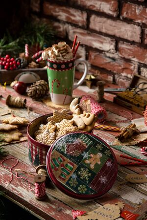 homemade delicious gingerbread cookies in vintage gift round metal box with christmas ornaments on wooden rustic red table with cup of coffee with foam, christmas tree branches opposite brick wall Foto de archivo - 132619956