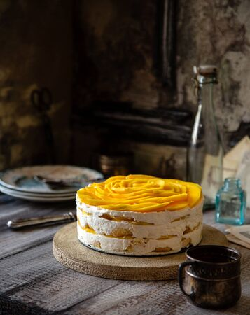 homemade whole round tiramisu cake with white whipped cream and slices of ripe juicy mango on top stands on grey wooden table opposite concrete wall