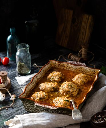 homemade tasty meatballs or cutlets from minced meat in tomato sauce in ceramic baking pan on rustic wooden table with grey napkin, vintage bottles, tomatoes