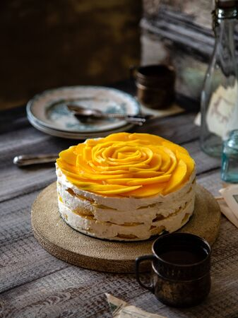 homemade whole round tiramisu cake with white whipped cream and slices of ripe juicy mango on top stands on grey wooden table opposite concrete wall Foto de archivo - 132563708