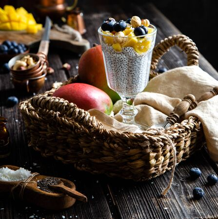 homemade tall beautiful glass with chia pudding with blueberries, mango slices, nuts on top stands in straw wicker basket on rustic table with fruits and nuts 写真素材