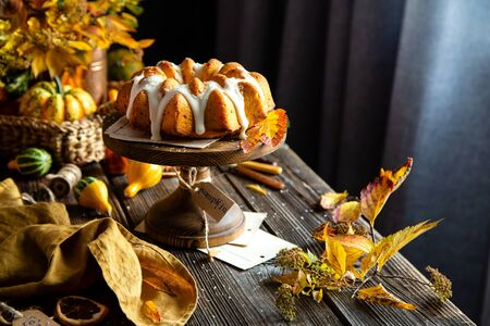 homemade tasty baked bundt pumpkin cake with glaze on top on wooden cake stand on rustic table with assorted small pumpkins, bouquet of autumn colorful leaves, orange napkin