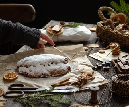 tasty homemade traditional christmas dessert stollen with dried berries and nuts on parchment in woman hand on wooden rustic table with spices, orange slices, Christmas tree branches, selective focus 写真素材