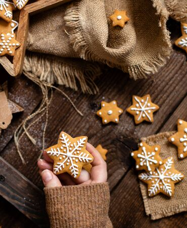 overhead shot of christmas snowflakes shaped orange cookies with beautiful icing decoration in woman hand on rustic brown table with sackcloth 写真素材