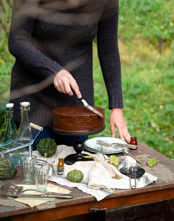 beautiful outdoor still life in autumn garden with woman smears the cake on wooden cake stand with chocolate cream stands on rustic wooden table with grey napkin, vintage bottles, glasses 写真素材