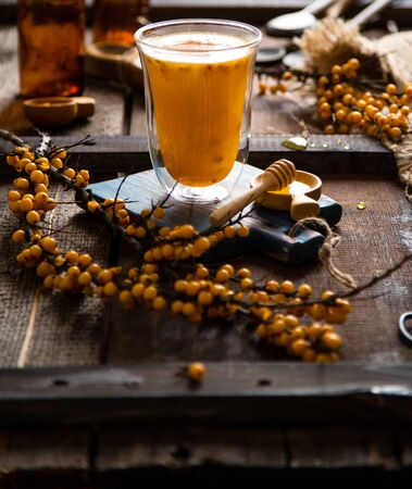 homemade cozy hot drink with sea buckthorn berries and honey in tall glass stands on wooden board on rustic table with tree branches, honey, sackcloth