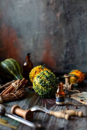 assorted mini pumpkins on rustic wooden table with cinnamon sticks, bottles, spoons opposite concrete wall, selective focus, thanksgiving card