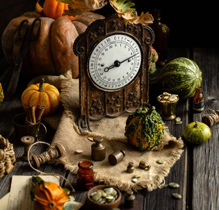 autumn thanksgiving still life photography with vintage brass scales, weights and assorted green, yellow, orange pumpkins