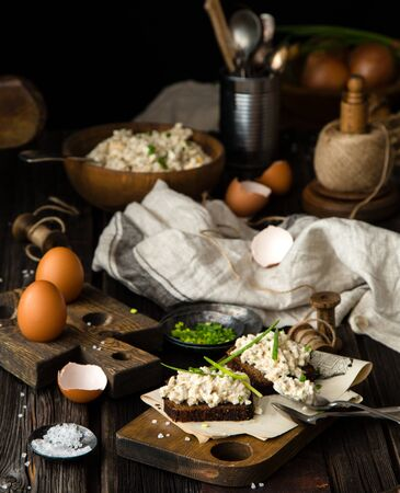 homemade tasty salad with hard boiled eggs, potato, green onion, mayonnaise in wooden bowl and on slices of bread on chopping board stands on rustic table with eggs, napkin, onion, selective focus