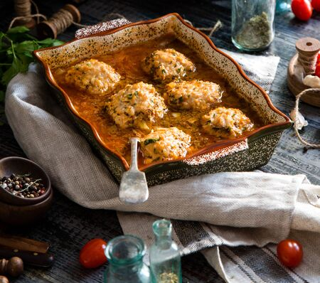 homemade tasty meatballs or cutlets from minced meat in tomato sauce in ceramic baking pan on rustic wooden table with grey napkin, vintage bottles, tomatoes Foto de archivo - 132563796