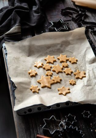 unbaked christmas gingerbread cookies on baking tray with parchment on rustic wooden table with rolling pin, flour and cookie cutters