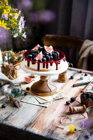 homemade tasty whole cheesecake decorated with figs, blackberries, blueberries and purple sauce on top served on wooden cake stand on grey table with flowers and berries, selective focus