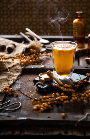 homemade cozy hot drink with sea buckthorn berries, honey and steam in tall glass stands on wooden board on rustic table with tree branches, honey, sackcloth